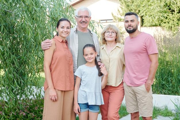 夏の日に近代的な公園で一緒に立っている5人家族のミディアムショット