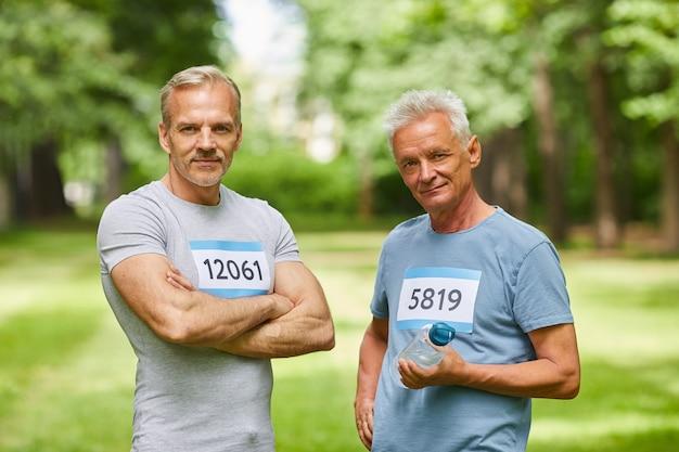 カメラを見ながら一緒に立っている、夏のマラソンの参加者である2人のハンサムな年配の成人男性のミディアムポートレート