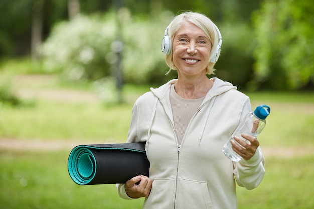 Medium portrait shot of happy aged woman wearing white headphones holding yoga mat and bottle of water smiling at camera