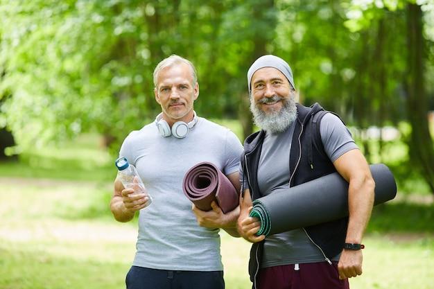 カメラを見ているヨガマットを持って公園で時間を過ごす2人の楽しいシニアスポーツマンのミディアムポートレートショット