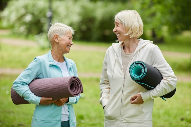 Medium portrait of two cheerful female friends wearing sports outfits holding yoga mats spending time together in park