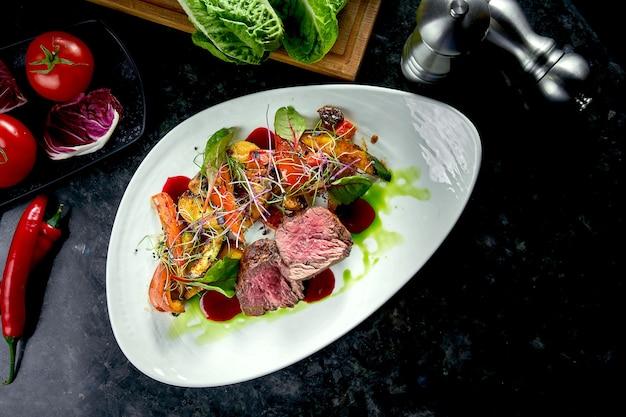 ミディアムレアのビーフメダリオンと野菜の付け合わせ、白いプレートでお召し上がりいただけます。暗い大理石のテーブル。バーベキュー肉、レストラン料理。美味しいステーキ