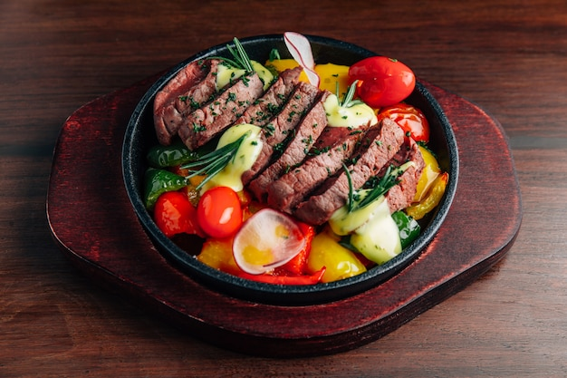 Medium rare beef steak served on hot plate with tomato, bell pepper, radish and rosemary.