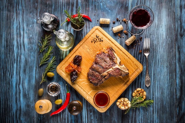 Medium rare grilled t-bone steak on rustic wooden background with rosemary and spices