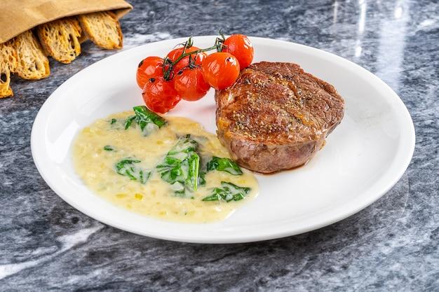 Medium rare ribeye steak doneness with tomato and white sauce