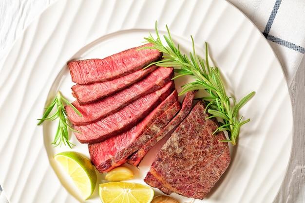 Обжаренный и нарезанный ломтиками стейк из говядины средней прожарки, подается на белой тарелке с дольками розмарина и лайма на белом деревянном столе, вид сверху, крупный план