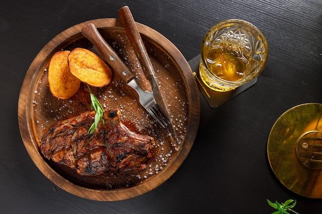 ミディアムレアのステーキ骨付き子牛のリブとジャガイモの木製プレート