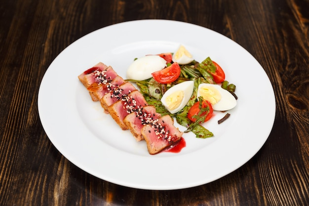 Medium rear beef steak sliced and drizzled with sesame sauce on white plate. garnish with boiled asparagus, eggs and tomatoes.