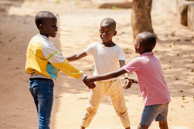 一緒に遊ぶミディアムショットのアフリカの男の子