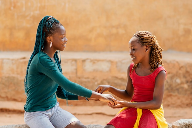 ミディアムショットのアフリカの女の子を一緒に