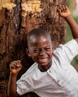 木の近くのミディアムショットアフリカの子供