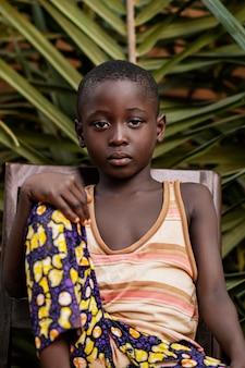 중간 샷 아프리카 아이 의자에 포즈