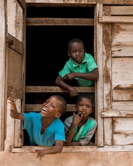 ウィンドウでミディアムショットのアフリカの子供たち