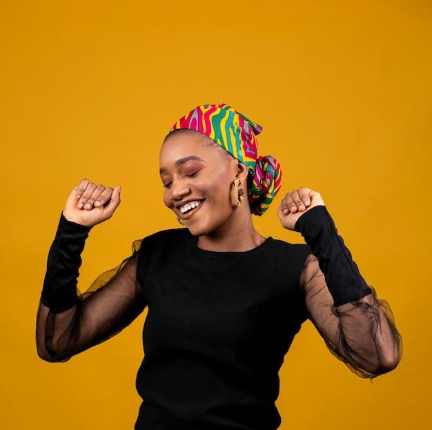Medium shot african woman dancing alone