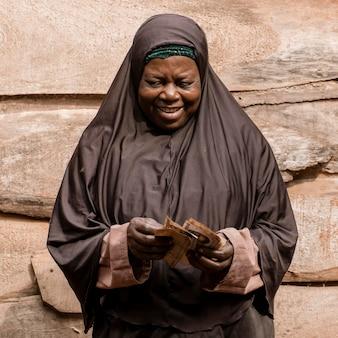 Среднего выстрела африканская женщина, держащая деньги