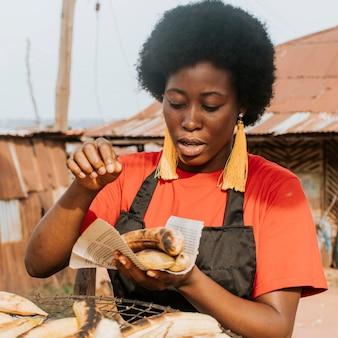 ミディアムショットのアフリカの女性が食べ物を作る