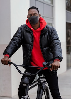 Medium shot afro-american man and his bicycle