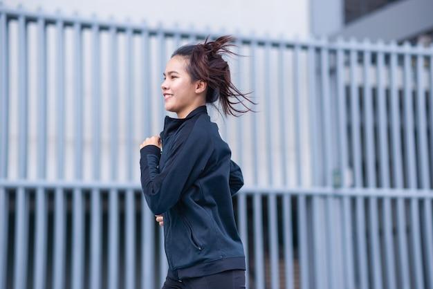 ミディアム ショットのアジアの美しい若い女性の黒のスーツで幸せなランニングや屋外でのジョギング