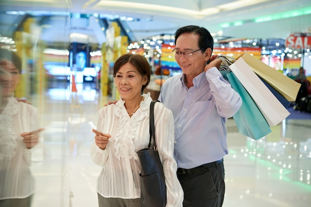 Medium shot of asian middle aged couple window shopping at a mall, man holding  shop bags