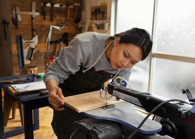 Donna asiatica del colpo medio che lavora con il legno