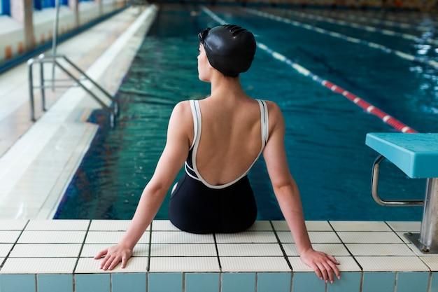 Спортсмен среднего роста сидит возле бассейна