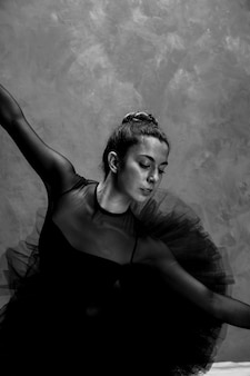 Medium shot ballerina bending grayscale
