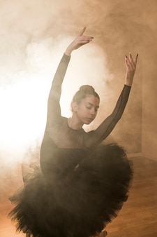 Medium shot ballerina posing in smoke