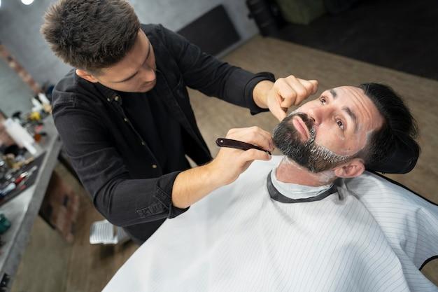 Medium shot barber grooming man