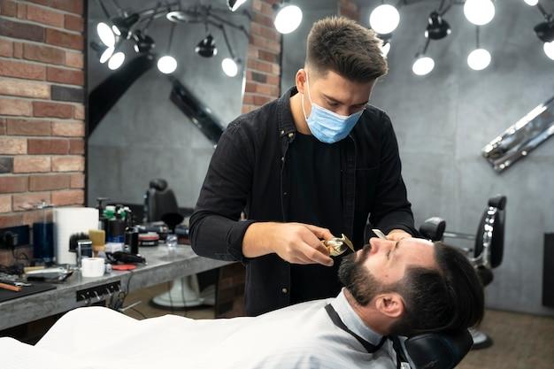 Medium shot barber wearing face mask