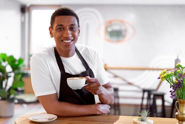 Medium shot barista holding coffee cup