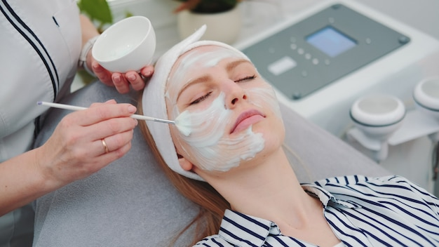 Medium shot of beautician putting cream mask on woman's face at beauty salon