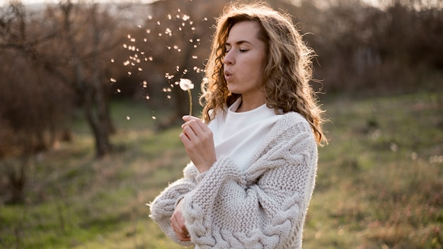 Medium shot of beautiful girl blowing a dandelion