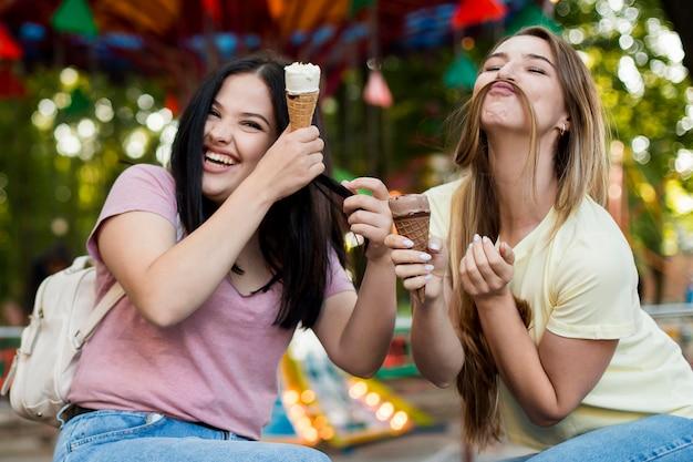 ミディアムショットのベストフレンドがアイスクリームを楽しみ、楽しいポーズをとる