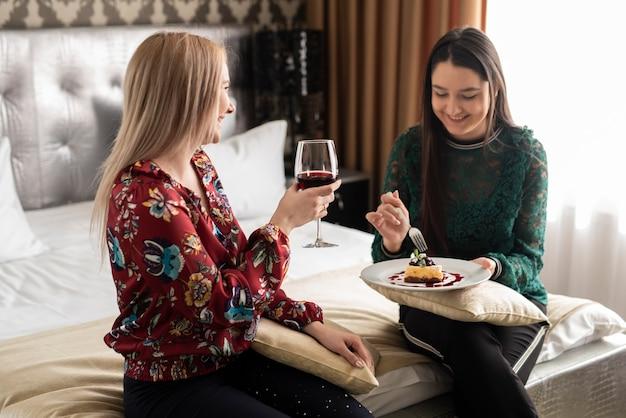 Medium shot best friends enjoying some wine and food