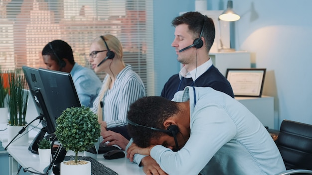 Medium shot of black customer support operator falling asleep on his table in call center