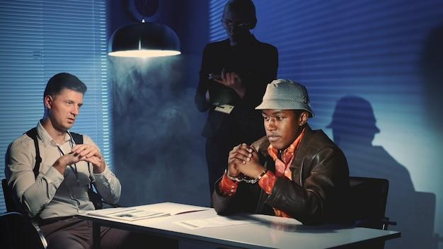 Medium shot of black prisoner in handcuffs having interview with caucasian detective in interrogation room