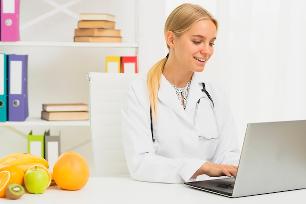Medium shot blonde doctor with laptop