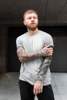 Medium shot blonde man with tattoos