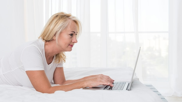 Medium shot blonde woman in bed with laptop