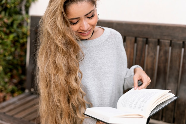 Medium shot blonde woman reading a book
