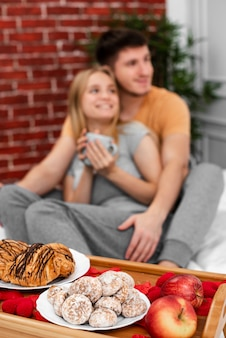 Medium shot blurred couple with breakfast in bed