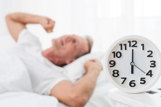 Medium shot blurred man waking up with clock