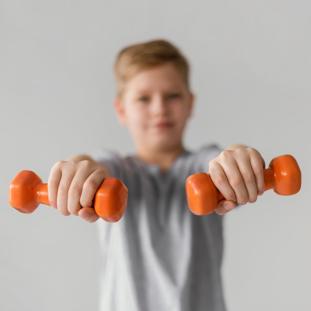 Medium shot blurry kid holding dumbbells