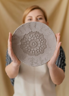 Medium shot blurry woman holding plate