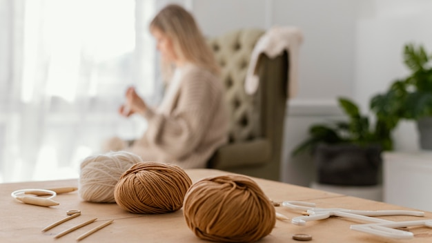 Medium shot blurry woman knitting indoors