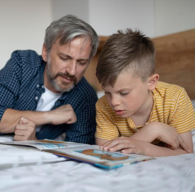 중간 샷 남자 아이 및 남자 독서 모드
