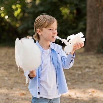 綿菓子を食べるミディアムショットの少年