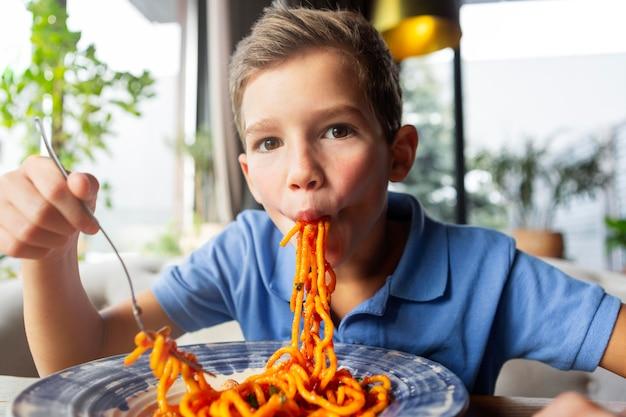スパゲッティを食べるミディアムショットの少年