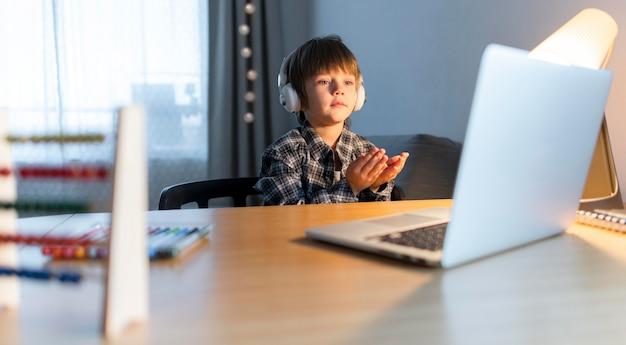 Medium shot of boy having virtual courses on laptop