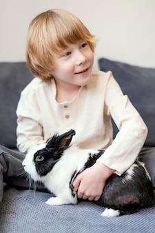 Средний выстрел мальчик держит кролика